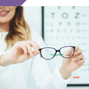 Woman holding reading glasses in front of dioptre chart.