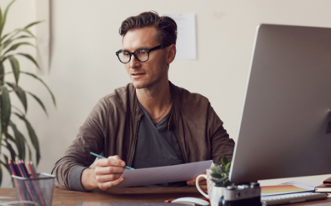 Man sat at laptop wearing Varilux Comfort Max lenses